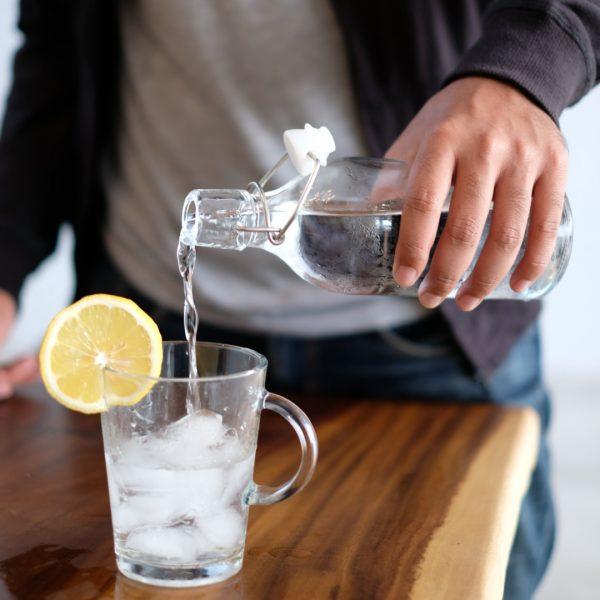 Eau versée dans un verre avec de la glace et citron Maple 3