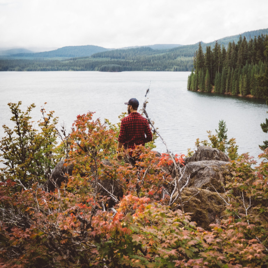 Homme habillé en chemise rouge au bord d'un lac